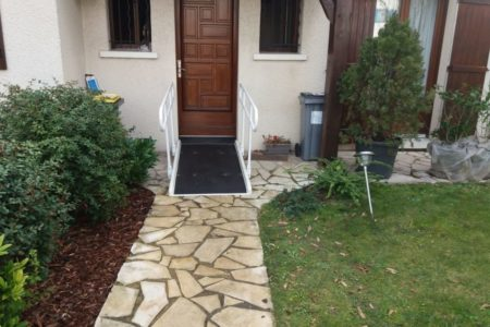 Access ramp for person with reduced mobility at the entrance of a house with standard access ramp and two handrails