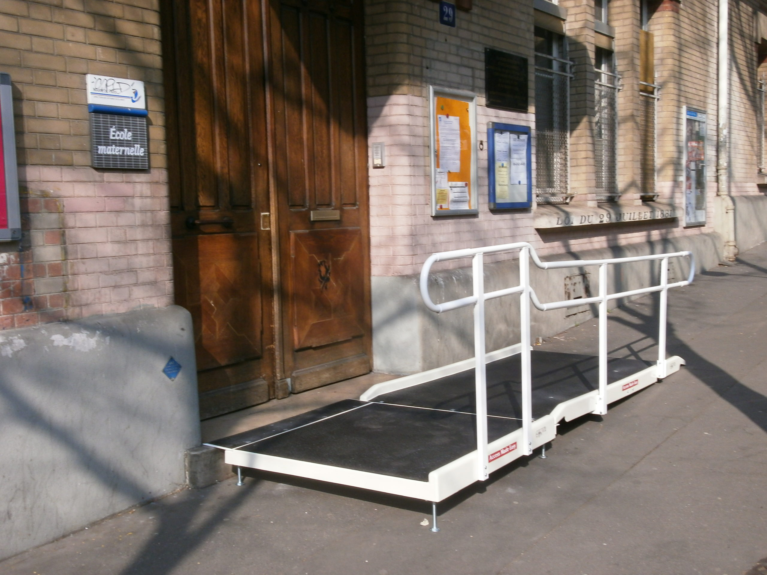 Accessibility of a nursery school for people with reduced mobility with a standard fibreglass ramp and one handrail and a platform